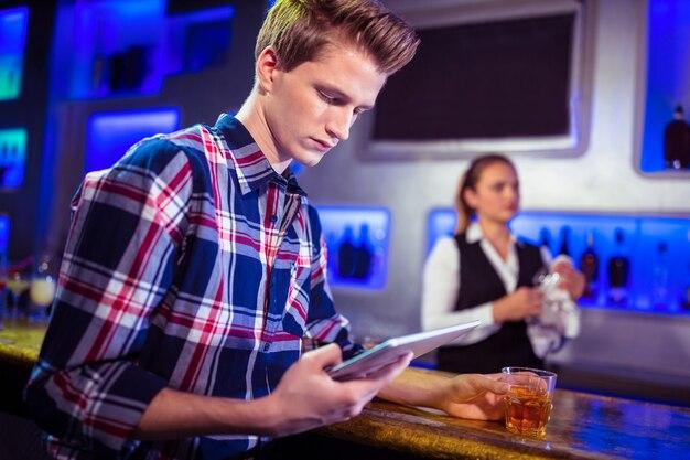 Mężczyzna używa cyfrową pastylkę z barmanu działaniem