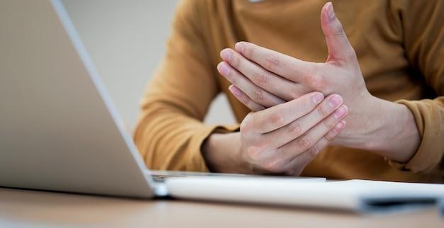 Mężczyzna używa dłoni do masowania dłoni w celu złagodzenia bólu po ciężkiej pracy