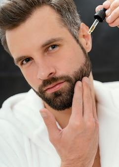 Mężczyzna używa do twarzy naturalnych olejków