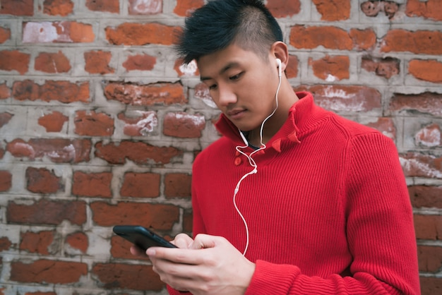 Mężczyzna używa jego telefon komórkowego z słuchawkami.
