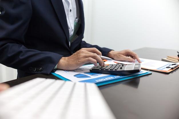 Mężczyzna używa kalkulatora i pisać robi notatce z kalkuluje.