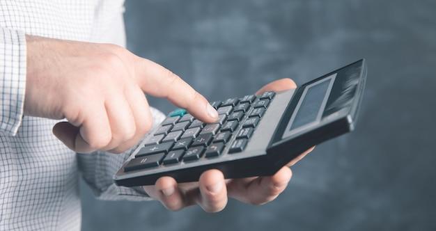 Mężczyzna używa kalkulatora.