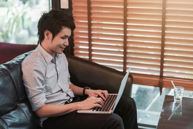 Mężczyzna używa laptop w kawiarni