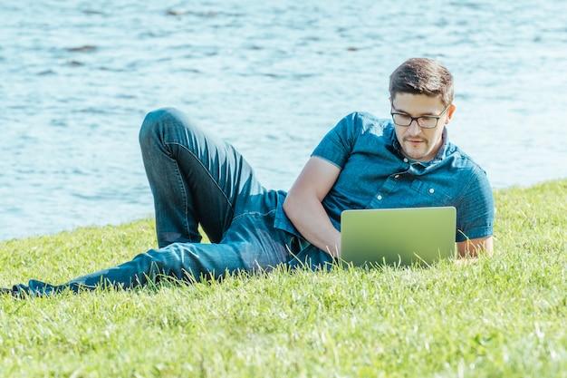 Mężczyzna używa laptop w miasto parku