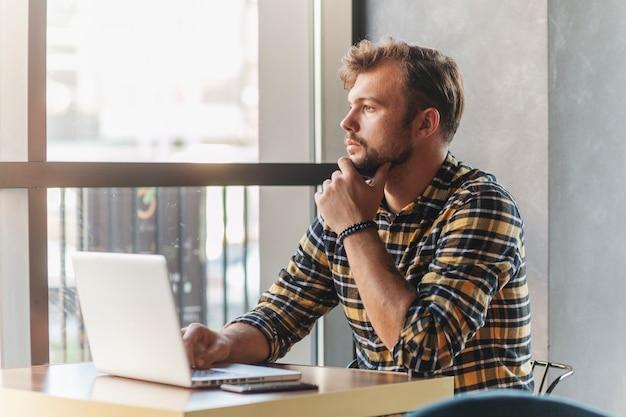 Mężczyzna używa laptop w sklep z kawą
