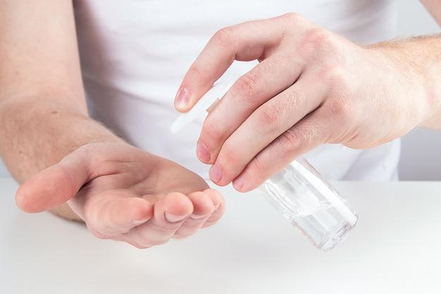 Mężczyzna używa małego przenośnego antybakteryjnego środka dezynfekującego do rąk.