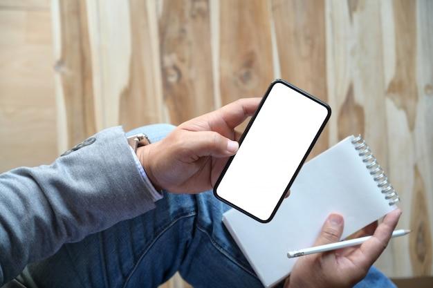 Mężczyzna używa mobilnego smartphone podczas pisać notatce