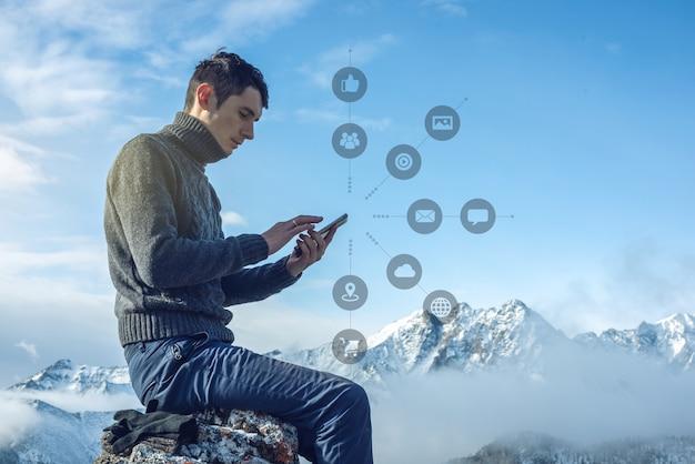Mężczyzna używa smartfona, aby uzyskać dostęp do cyfrowych mediów społecznościowych w internecie