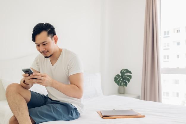 Mężczyzna używa smartfona na łóżku w koncepcji relaksu.