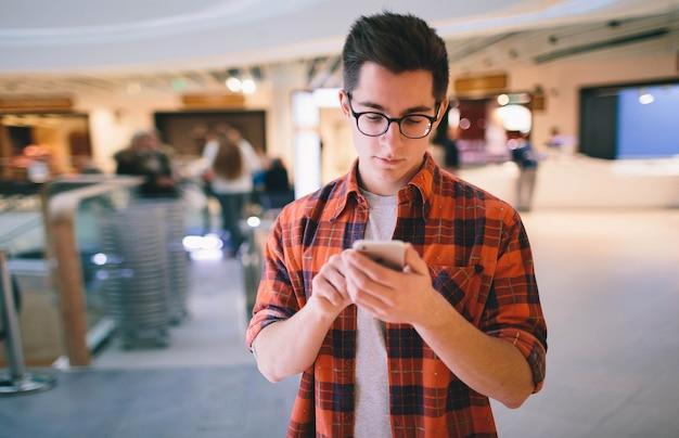 Mężczyzna używa smartfona na ścianie centrum handlowego