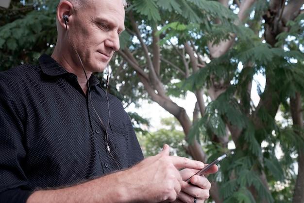 Mężczyzna używa smartphone w parku