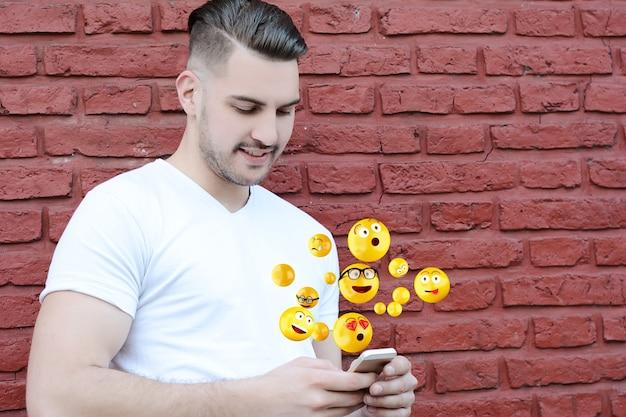 Mężczyzna używa smartphone wysyłania emoji.