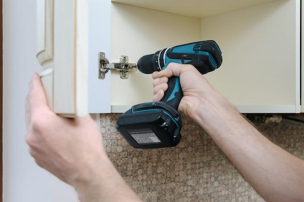 Mężczyzna używa śrubokręta do regulacji zakrzywionych drzwi szafki.