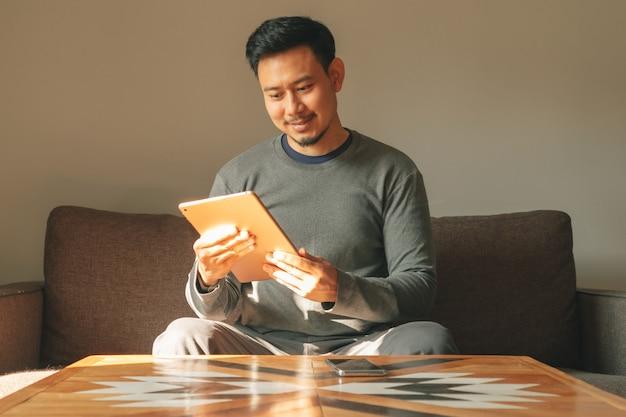 Mężczyzna używa swojego inteligentnego tabletu w swoim mieszkaniu.