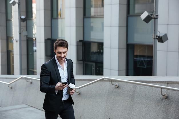 Mężczyzna używa telefon i pije kawę