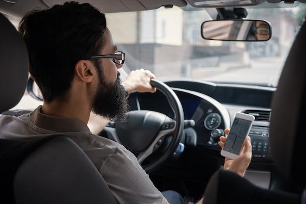 Mężczyzna używa telefon komórkowego podczas jazdy.