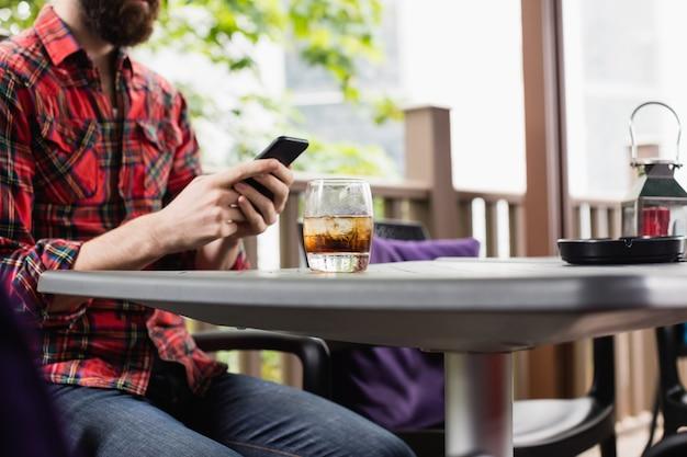 Mężczyzna używa telefon komórkowego w barze