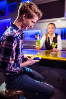 Mężczyzna używa telefon komórkowego z barman pozycją