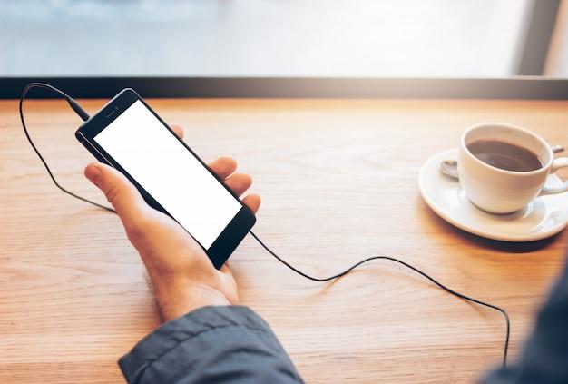 Mężczyzna używa telefon komórkowego z hełmofonami w kawiarni