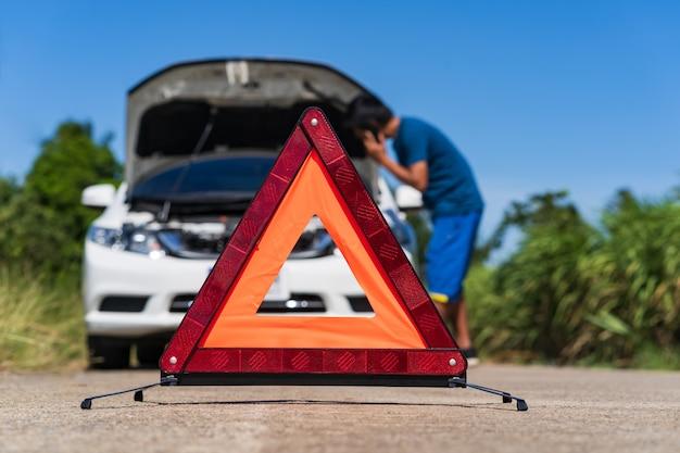 Mężczyzna używa telefon podczas gdy mieć problemowego samochód i czerwonego trójboka znak ostrzegawczy na drodze