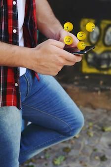 Mężczyzna używa telefonu dosłania emoja