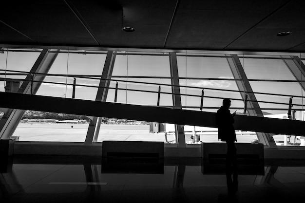 Mężczyzna używa telefonu komórkowego na lotnisku. biznesmena czekanie dla wylotowego lota przy lotniskowym terminal. czarno-biała scena nowoczesnej architektury szkła wewnętrznego.