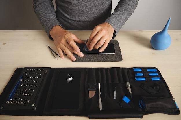 Mężczyzna używa wtyczki próżniowej, aby usunąć ekran z uszkodzonego telefonu, jego zestaw narzędzi ze specjalnymi narzędziami w pobliżu