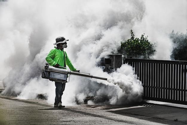 Mężczyzna używa zamgławiającej maszyny do kontrolowania niebezpiecznego od komarów