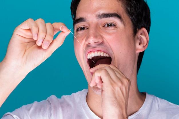 Mężczyzna używa zęby nici dentystycznej portret