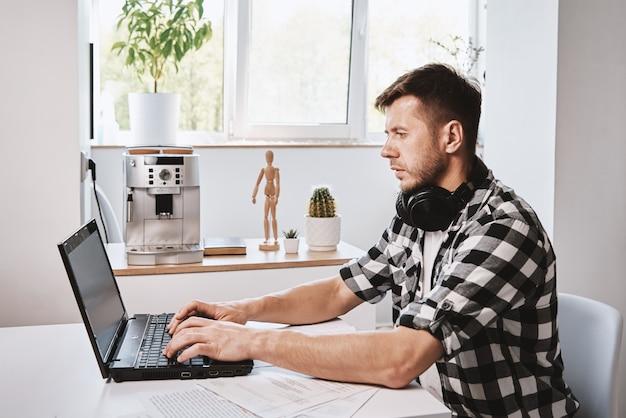 Mężczyzna używający laptopa w domowym biurze