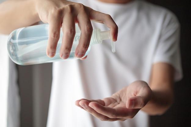 Mężczyzna używający odkażacza alkoholowego wcierania w żelu do czyszczenia rąk koncepcja zapobiegania koronawirusowi covid-19
