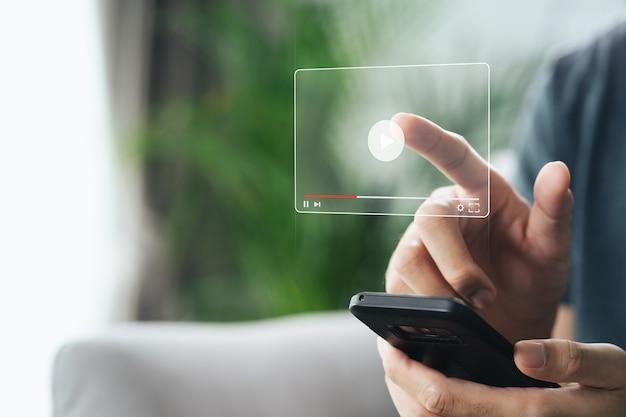 Mężczyzna używający smartfona do oglądania wideo w internecie, przesyłania strumieniowego online, zajęć online, twórcy treści