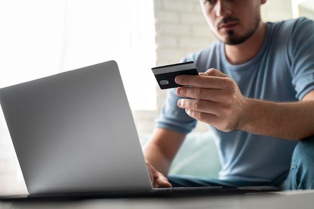 Mężczyzna używający swojej karty kredytowej do gry online o zamówienie