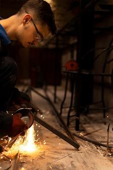 Mężczyzna używający szlifierki kątowej z iskrami
