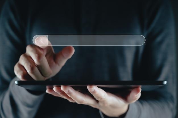 Mężczyzna używający tabletu do wyszukiwania informacji za pomocą paska wyszukiwania, przeglądarki internetowej, wyszukiwania danych, wyszukiwarki, koncepcji technologicznej