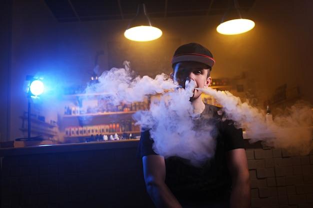 Mężczyzna vaping trzyma mod. chmura pary w sklepie z vape.