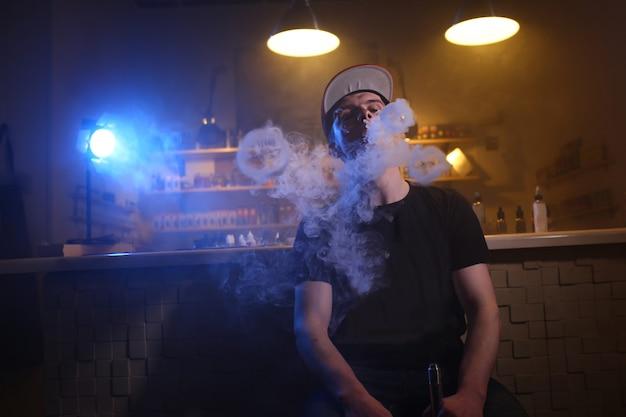 Mężczyzna vaping w chmurze pary w barze vape