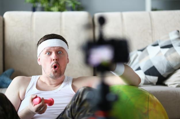 Mężczyzna vlogger trzyma hantle w swoim