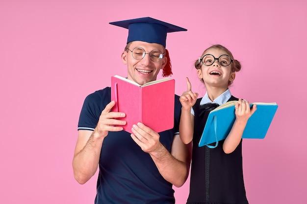 Mężczyzna w akademickim kapeluszu trzyma książkę, uczy się wraz ze śliczną preteen dziewczyną w mundurek szkolny. ojciec, córka odizolowywająca na menchii przestrzeń wewnątrz. miłość koncepcja dzień rodzicielstwa dzieciństwo rodziny