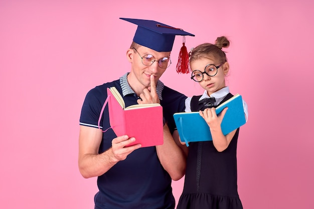 Mężczyzna w akademickim kapeluszu trzyma książkę, uczy się wraz ze śliczną preteen dziewczyną w mundurku szkolnym. ojcuje, córka odizolowywająca na różowym tle w studiu. miłość koncepcja dzień rodzicielstwa dzieciństwo rodziny.