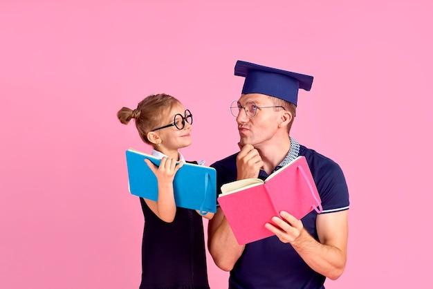 Mężczyzna w akademickim kapeluszu trzymając książkę, uczyć się razem z uroczą dziewczyną preteen w szkolnym mundurku