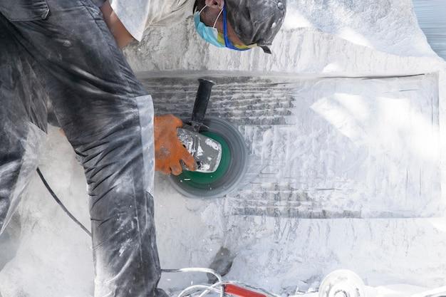 Mężczyzna w akcesoriach ochronnych pracuje nad obróbką białego dużego kamienia.