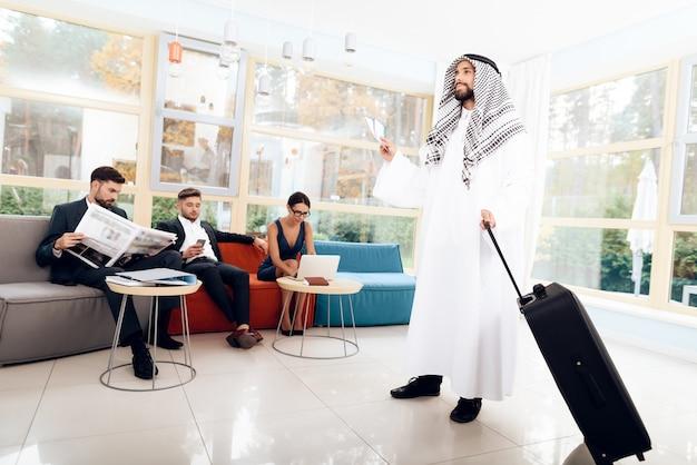 Mężczyzna w arabskich ubraniach trzyma walizkę.