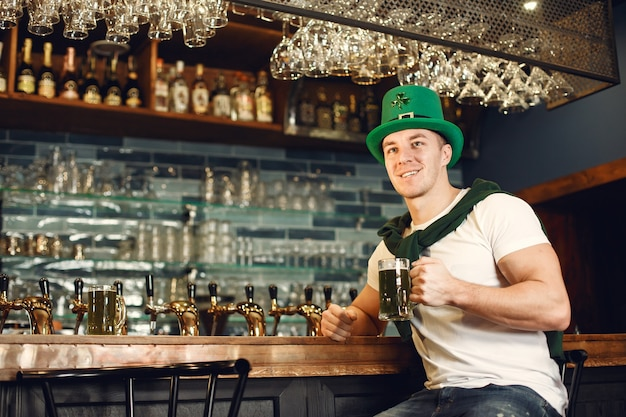 Mężczyzna w barze z piwem. guy obchodzi dzień świętego patryka. mężczyzna w zielonym kapeluszu.