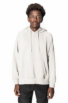 Mężczyzna w beżowej bluzie z kapturem, zimowa sesja odzieży młodzieżowej
