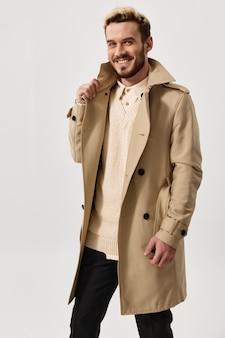 Mężczyzna w beżowym płaszczu i lekkim swetrze na na białym tle portret pozowanie ubrania