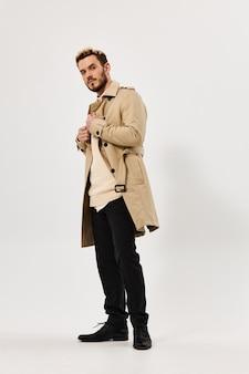 Mężczyzna w beżowym płaszczu wygląda na bok w nowoczesnym stylu