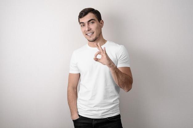 Mężczyzna w białej koszula pokazuje ok znaka