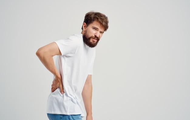 Mężczyzna w białej koszulce dotyka pleców z bólem kręgosłupa dłoni