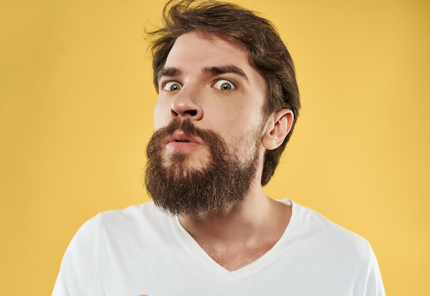 Mężczyzna w białej koszulce gestykuluje złość studio